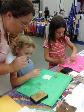 Mom does the Adrinkra stamp  activity with her children at the Original Creative Festival in Sharonville, Ohio.