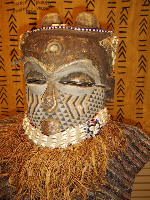 West African mask embellished with metal, cowrie shells, cotton, semi precious beads, paint and grass. UGRR Secret Quilt Code Museum African Collection, Teresa R. Kemp's Traveling Exhibit artifacts. Call (404) 468-7050 today to schedule your traveling cultural exhibit today.