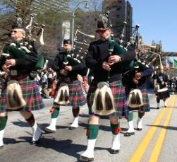 Instruments called bag pipes are being played at the Irish Festival. They play for celebrations and for funerals. The men are dressed in plaid kilts. There is a language in plaid fabrics.