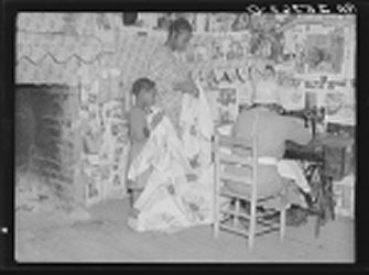 Gees Bend Alabama USA African American family sewing a quilt.