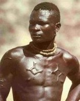 Scarification Art are marks of beauty in West Africa. He has the UGRR Quilt Code patterns cut into His skin on his chest and arms.